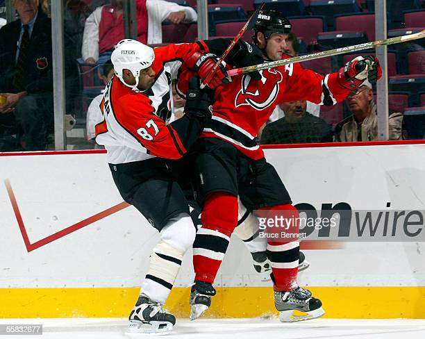 Defenseman Colin White of the New Jersey Devils gets tangled with left wing Donald Brashear of the Philadelphia Flyers during a preseason game at the...