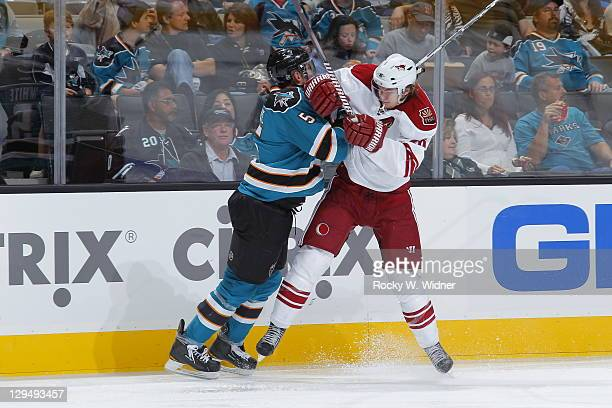 Defenseman Colin White of the San Jose Sharks collides with left wing Viktor Tikhonov of the Phoenix Coyotes at the HP Pavilion on September 24 2011...
