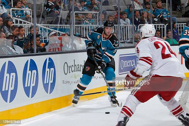 Defenseman Colin White of the San Jose Sharks passes the puck against left wing Kyle Chipchura of the Phoenix Coyotes at the HP Pavilion on September...