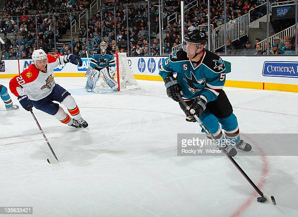 Defenseman Colin White of the San Jose Sharks skates with the puck against left wing Sean Bergenheim of the Florida Panthers at the HP Pavilion on...