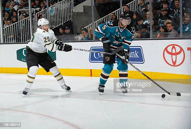 Defenseman Colin White of the San Jose Sharks skates with the puck against right wing Radek Dvorak of the Dallas Stars at the HP Pavilion on December...