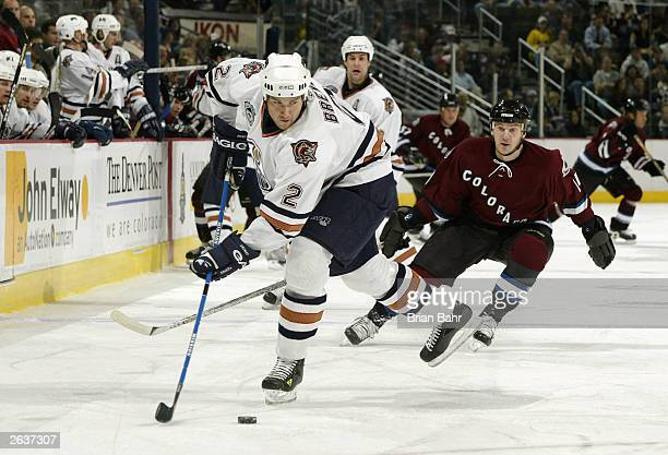 Defenseman Eric Brewer of the Edmonton Oilers moves to turn the puck back onto offense under pressure from Andrei Nikolishin of the Colorado...