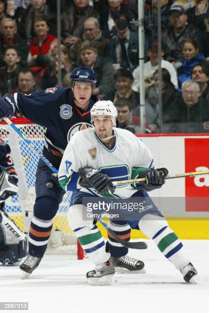 Defenseman Eric Brewer of the Edmonton Oilers pressures right wing Jason King of the Vancouver Canucks during the game at General Motors Place on...