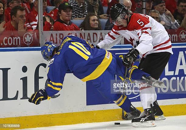 Defenseman Erik Gudbranson of Canada knocks down forward Johan Larsson of Sweden during the 2011 IIHF World U20 Championship game between Canada and...