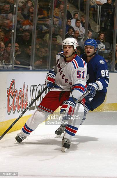Defenseman Fedor Tyutin of the New York Rangers and right wing Jeff O'Neill of the Toronto Maple Leafs battle for position as they wait for the puck...
