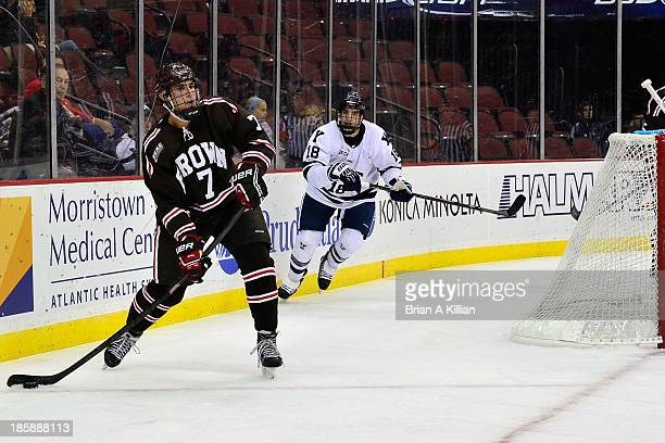 Defenseman Jake Goldberg of the Brown Bears clears the puck as left wing Kenny Agostino of the Yale Bulldogs pursues at Prudential Center on October...