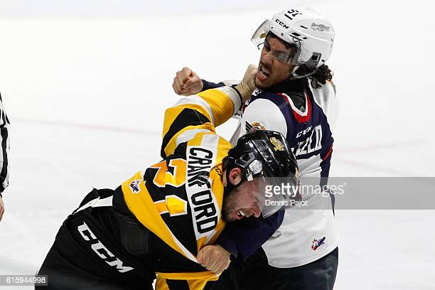 Defenseman Jalen Chatfield of the Windsor Spitfires delivers a punch during a fight against forward Ryan Cranford of the Kingston Frontenacs on...