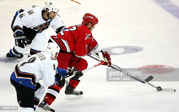 Defenseman Jamie Heward and left wing Matt Pettinger of the Washington Capitals chase down center Eric Staal of the Carolina Hurricanes during their...