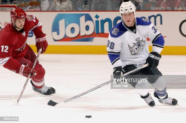Defenseman Kevin Dallman of the Los Angeles Kings looks to pass the puck up ice while Craig Weller of the Phoenix Coyotes tries to stop him during...