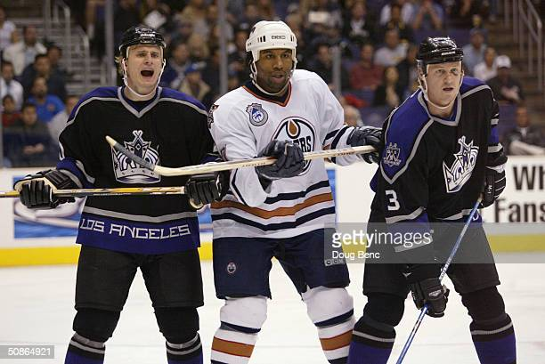 Defenseman Nathan Dempsey and defenseman Aaron Miller of the Los Angeles Kings flank right wing Georges Laraque of the Edmonton Oilers during the...
