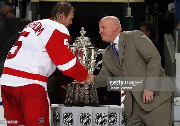 Defenseman Nicklas Lidstrom of the Detroit Red Wings shakes hands with Bill Daly deputy commisioner of the NHL after he Clarence S Campbell Bowl was...