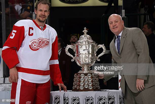 Defenseman Nicklas Lidstrom of the Detroit Red Wings stands next to the Clarence S Campbell Bowl with Bill Daly deputy commisioner of the NHL after...