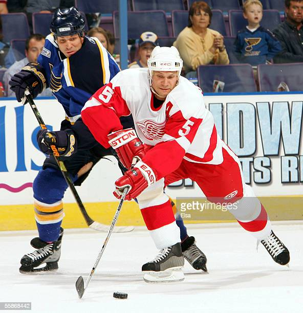 Defenseman Nicklas Lidstrom of the Detroit Red Wings tries to keep the puck from center Doug Weight of the St Louis Blues on October 6 2005 at the...