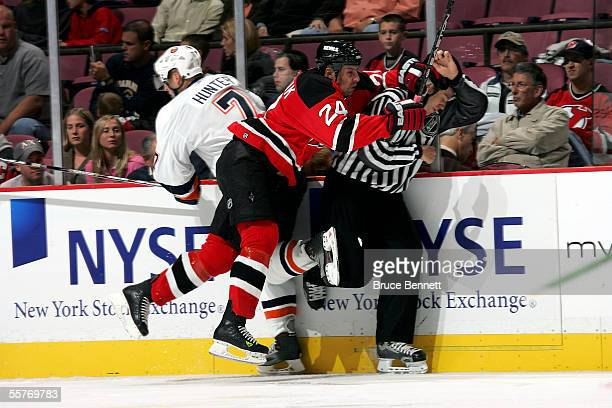 Defenseman Richard Matvichuk of the New Jersey Devils misses his check on right wing Trent Hunter of the New York Islanders hitting linesman Pat...