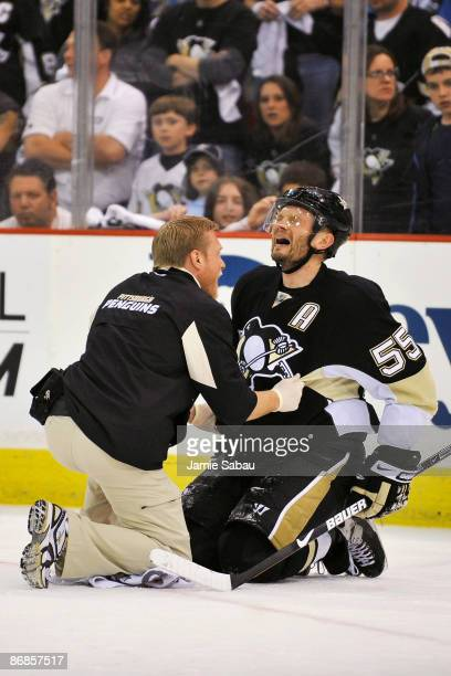 Defenseman Sergei Gonchar of the Pittsburgh Penguins is attended to by a trainer after he was injured in a collision with Alex Ovechkin of the...