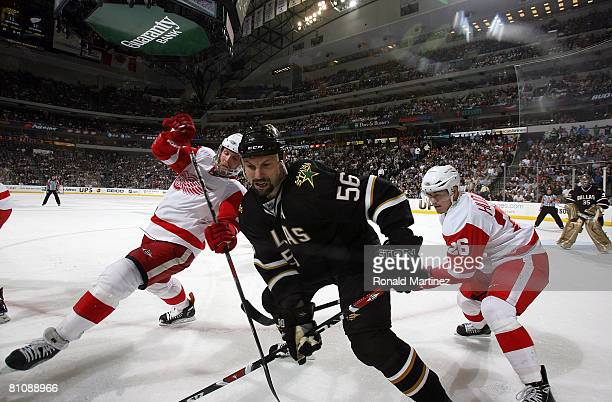 Defenseman Sergei Zubov of the Dallas Stars works the puck on the boards against Dan Cleary and Jiri Hudler of the Detroit Red Wings during game four...