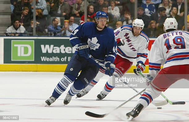 Defenseman Staffan Kronwall of the Toronto Maple Leafs skates with the puck as Blair Betts and Jason Ward of the New York Rangers defend during their...