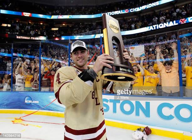 Defenseman Tommy Cross of the Boston College Eagles holds up the championship trophy after defeating the Ferris State Bulldogs during the NCAA...
