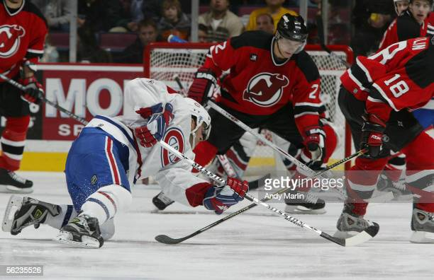 Defenseman Vladimir Malakhov of the New Jersey Devils plays the puck as center Mike Ribeiro of the Montreal Canadiens falls to the ice in NHL action...