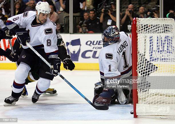 Defenseman Willie Mitchell of the Vancouver Canucks sweeps the puck out of the net before it crosses the line on a shot by Mike Ribeiro of the Dallas...