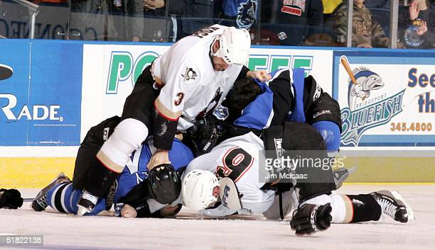 Defensemen David Koci and Ryan Whitney of the WilkesBarre/Scranton Penguins fight against defenseman Richard Seeley of the Bridgeport Sound Tigers...