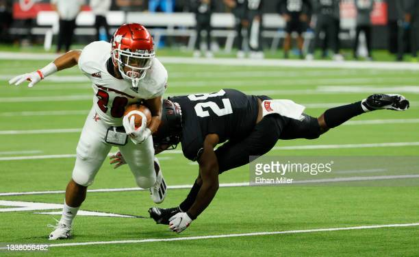 Defensive back Aaron Lewis of the UNLV Rebels tries to tackle running back Isaiah Lewis of the Eastern Washington Eagles during their game at...