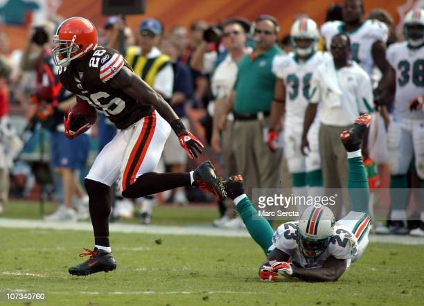 Defensive back Abram Elam of the Cleveland Browns intercepts the ball against Ronnie Brown of the Miami Dolphins at Sun Life Stadium on December 5...