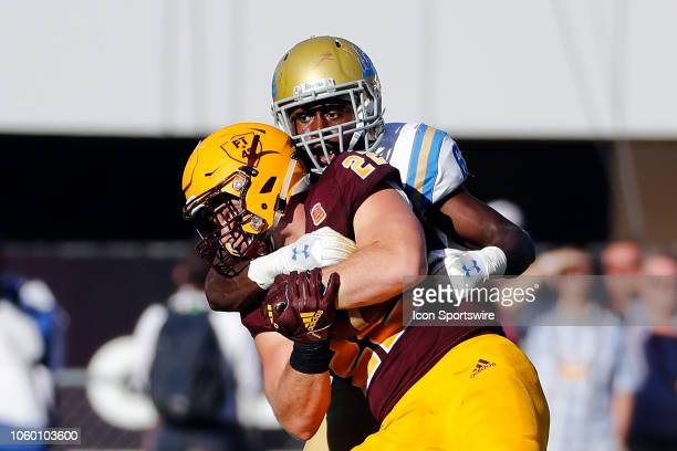 Defensive back Adarius Pickett of the UCLA Bruins tackles fullback Mark Cosgrove of the Arizona State Sun Devils during the second half of the...