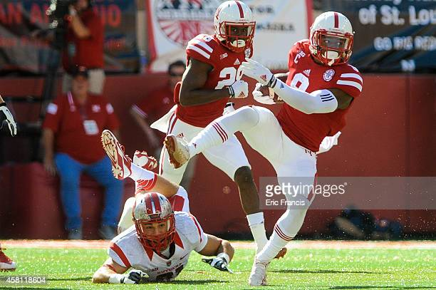 Defensive back Anthony Cioffi of the Rutgers Scarlet Knights tries to trip up running back Ameer Abdullah of the Nebraska Cornhuskers during the game...