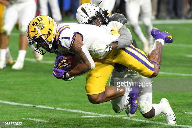 Defensive back Antwan Collier of the UCF Knights tackles wide receiver Ja'Marr Chase of the LSU Tigers during the fourth quarter of the PlayStation...
