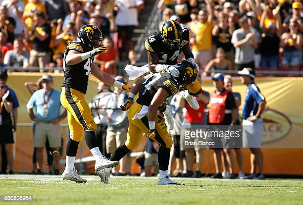 Defensive back Brandon Snyder of the Iowa Hawkeyes celebrates his interception with teammates defensive back Desmond King and linebacker Josey Jewell...