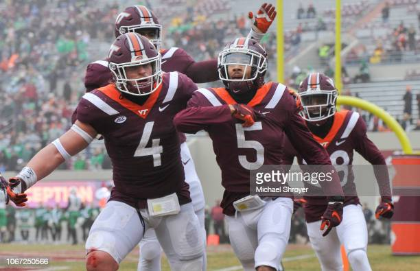 Defensive back Bryce Watts of the Virginia Tech Hokies celebrates his interception against the Marshall Thundering Herd with linebacker Dax...
