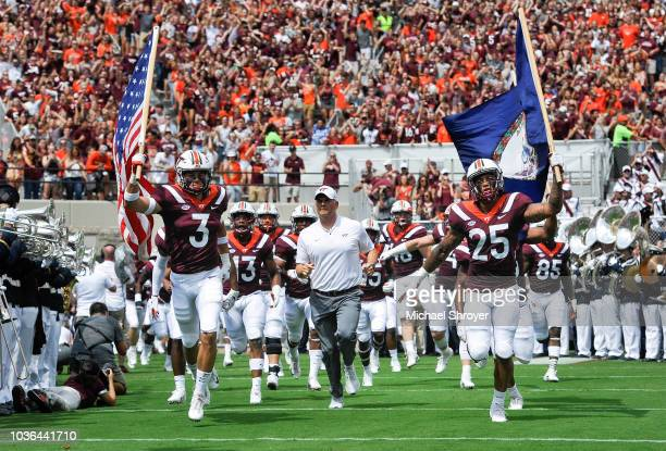 Defensive back Caleb Farley wide receiver Eric Kumah and head coach Justin Fuente of the Virginia Tech Hokies lead the team onto the field prior to...