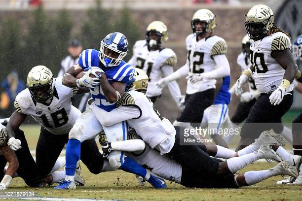 Defensive back Cameron Glenn of the Wake Forest Demon Deacons leads a tackle of running back Deon Jackson of the Duke Blue Devils during their...