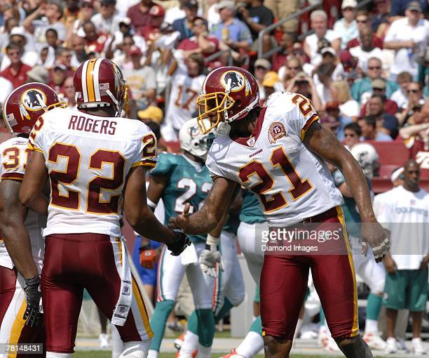 Defensive back Carlos Rogers shakes hands with safety Sean Taylor of the Wshington Redskins after the Redskins' defense stopped the Miami Dolphins...