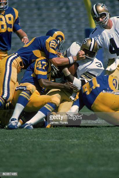 Defensive back Charlie Stukes and Steve Preece of the Los Angeles Rams team up to stop running back Jess Phillips of the New Orleans Saints at the...