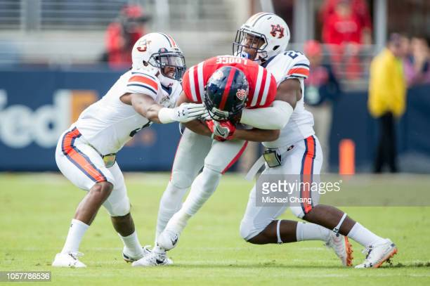 Defensive back Christian Tutt of the Auburn Tigers and defensive back Daniel Thomas of the Auburn Tigers tackle wide receiver DaMarkus Lodge of the...