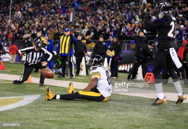 Defensive back Chykie Brown of the Baltimore Ravens celebrates as wide receiver Emmanuel Sanders of the Pittsburgh Steelers sits on the turf after...
