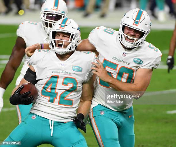 Defensive back Clayton Fejedelem and long snapper Blake Ferguson of the Miami Dolphins celebrate after Fejedelem gained 22 yards on a fake punt...