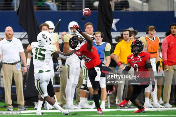 Defensive back Damarcus Fields of the Texas Tech Red Raiders deflects a pass intended for wide receiver Denzel Mims of the Baylor Bears and the ball...