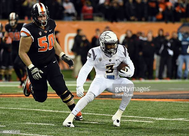 Defensive back Damarious Randall of the Arizona State Sun Devils runsback an interception as offensive lineman Josh Mitchell of the Oregon State...