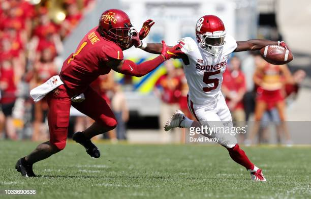 Defensive back D'Andre Payne of the Iowa State Cyclones drives wide receiver Marquise Brown of the Oklahoma Sooners ut of bounds as he rushed for...