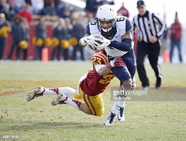 Defensive back Darian Cotton of the Iowa State Cyclones tackles wide receiver Daikiel Shorts of the West Virginia Mountaineers as he rushed for yards...