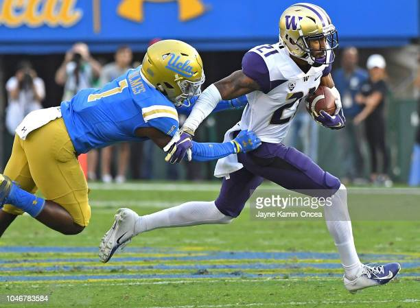 Defensive back Darnay Holmes of the UCLA Bruins chases down wide receiver Quinten Pounds of the Washington Huskies as he runs for a first down on a...