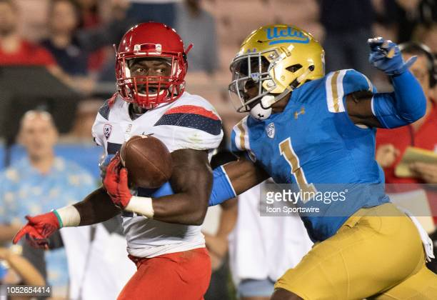 UCLA defensive back Darnay Holmes right forces a fumble to Arizona running back JJ Taylor during a college football game between the UCLA Bruins and...