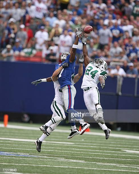 Defensive Back Darrelle Revis of the New York Jets breaks up a long pass intended for Wide Receiver Plaxico Burress of the New York Giants in a game...
