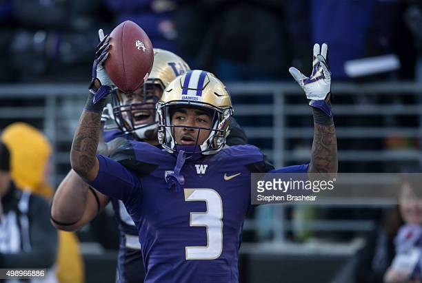 Defensive back Darren Gardenhire of the Washington Huskies celebrates scoring recovering a fumble and scoring a touchdown with defensive lineman...