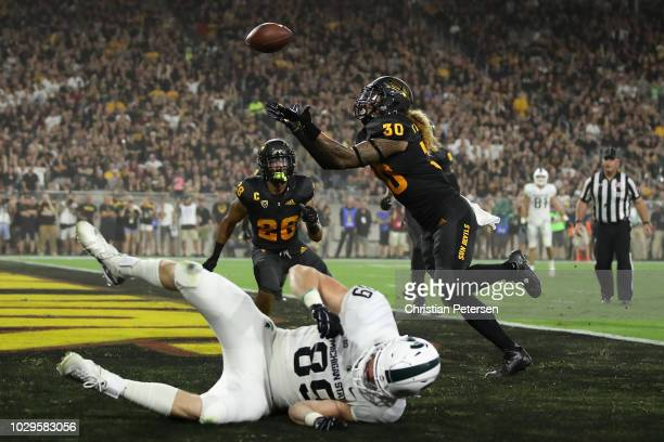 Defensive back Dasmond Tautalatasi of the Arizona State Sun Devils intercepts a pass intended for tight end Matt Dotson of the Michigan State...