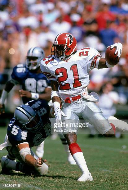 Defensive back Deion Sanders of the Atlanta Falcons in action carrying the ball avoiding the tackle of centre Tom Rafferty of the Dallas Cowboys...