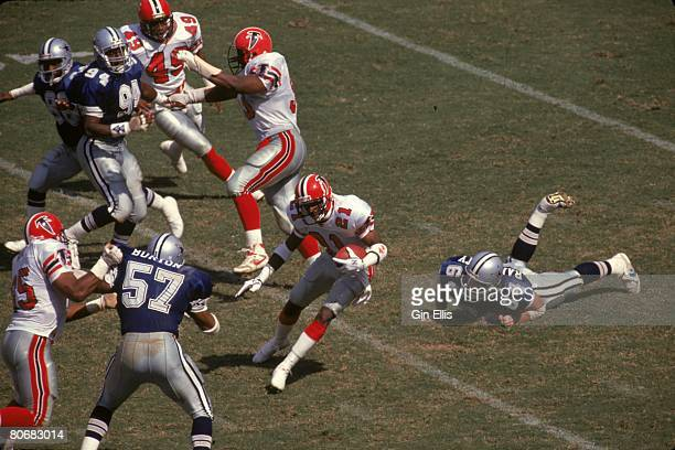 Defensive back Deion Sanders of the Atlanta Falcons returns a punt in an NFL game against the Dallas Cowboys at the Fulton County Stadium on...